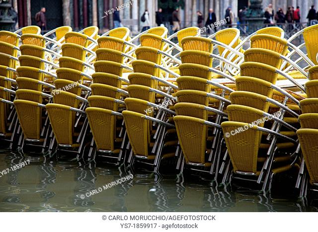 Quadri's reastaurant chairs during high tide in St  Mark's square, acqua alta, Venice, Italy, Europe