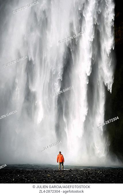 Iceland, Sudurland region, man in front of Skogafoss waterfall