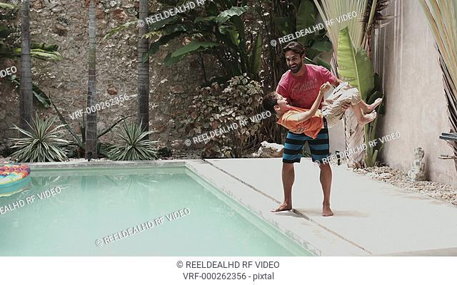 Father throwing son into swimming pool having fun