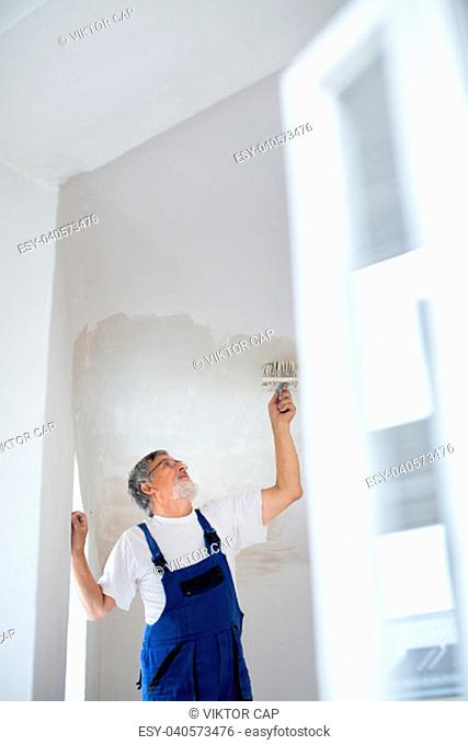 Senior painter man at work with a paint bucket, wall painting concept