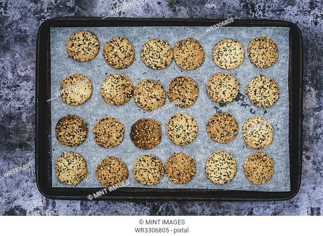 High angle close up of freshly baked seeded crackers on a baking tray