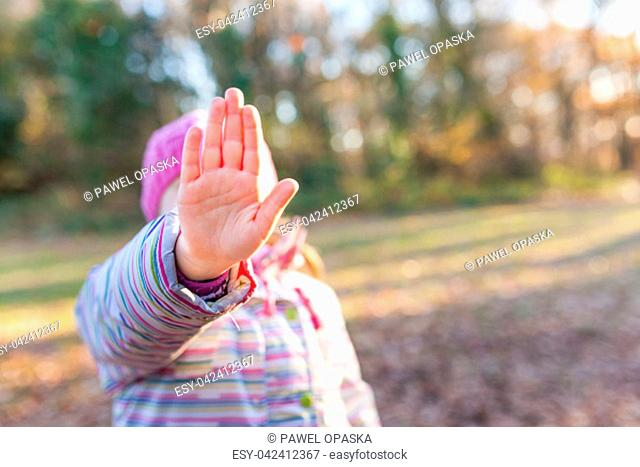 Portrait of young caucasian girl showing stop hand sign in front of her face
