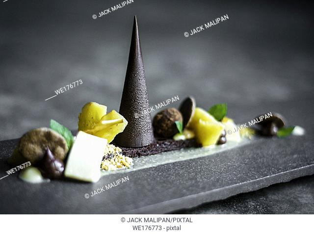 gourmet modern creative chocolate cake and dried fruit dessert dish on slate