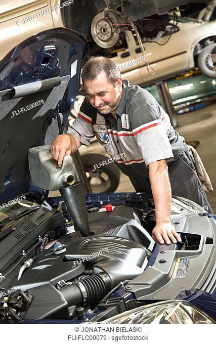 Mechanic filling oil under hood of car