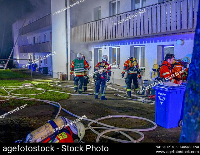 """17 December 2020, Baden-Wuerttemberg, Ellwangen: Firefighters work to fight a fire in front of an apartment building. (to dpa: """"""""Eleven injured by cellar fire..."""