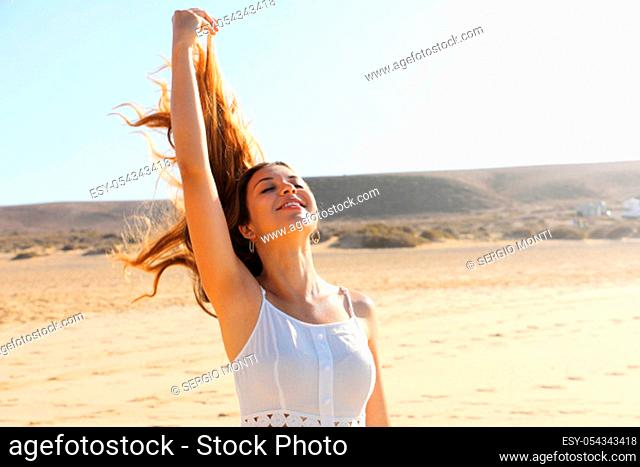 Carefree woman breathing fresh air on the beach with flying hair in the wind