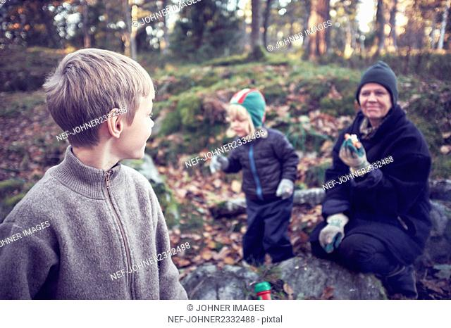 Grandmother with grandchildren picking mushrooms
