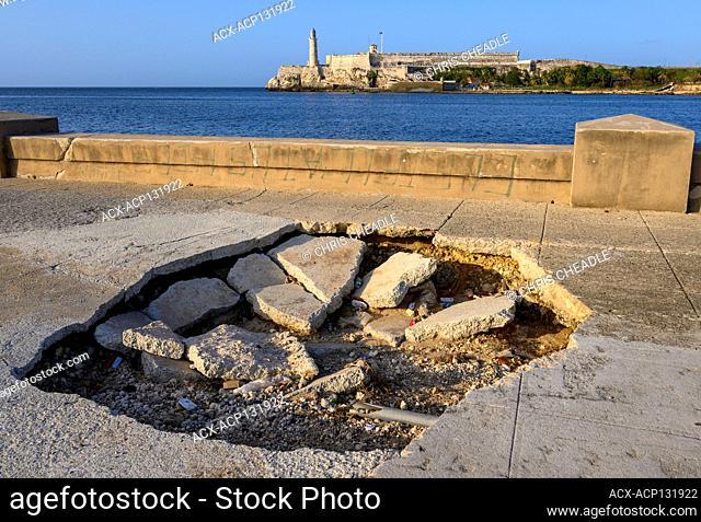 """Hole in sidewalk of the Malecon, El Castillo de los Tres Reyes Magos del Morro or simply """"El Morro"""" in the distance, Havana Vieja, Cuba"""