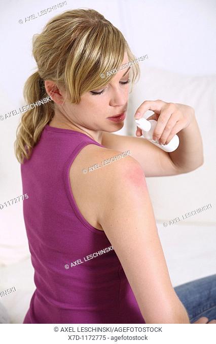 woman spraying against midge sting