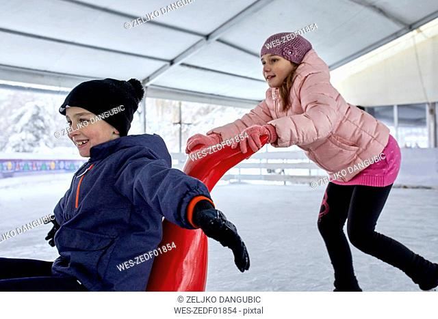Sister pushing brother on the ice rink,sitting on seal sledge