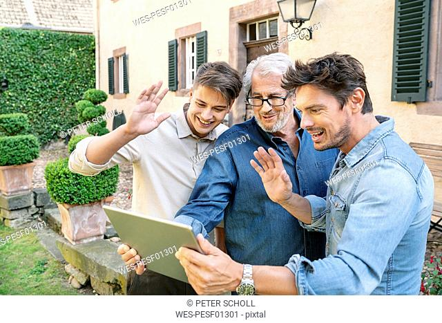 Three men of different age having a video chat via tablet in garden
