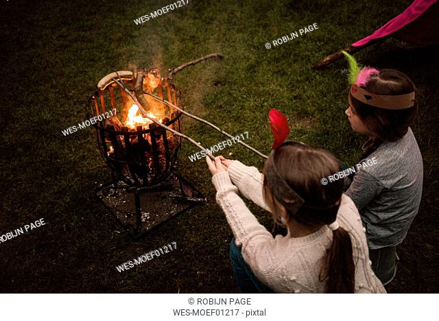 Two girls wearing feather headdress, grilling sausage over camp fire