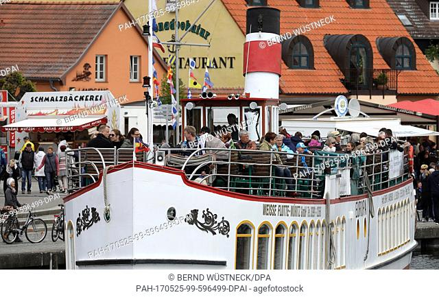 """Visitors set out on the steamer """"""""Europa"""""""" at the city harbour after the start of Mueritz Sail in Waren, Germany, 25 May 2017"""