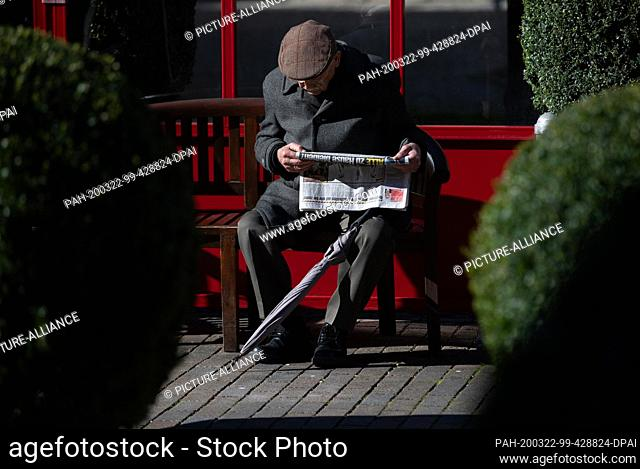 """22 March 2020, North Rhine-Westphalia, Bielefeld: """"""""Everybody stay home?"""""""" is the headline of a newspaper an elderly man reads on a bench"""