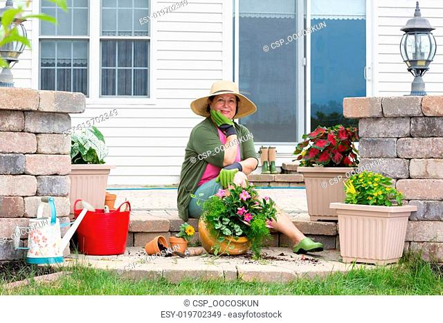 Grandmother potting up plants on her patio