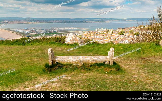 A stone bench on the South West Coast Path with view towards Fortuneswell and Chesil Beach, Isle of Portland, Jurassic Coast, Dorset