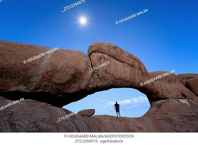 Landscape photo of a person standing in a natural arch below a full moon. Spitzkoppe, Erongo, Namibia