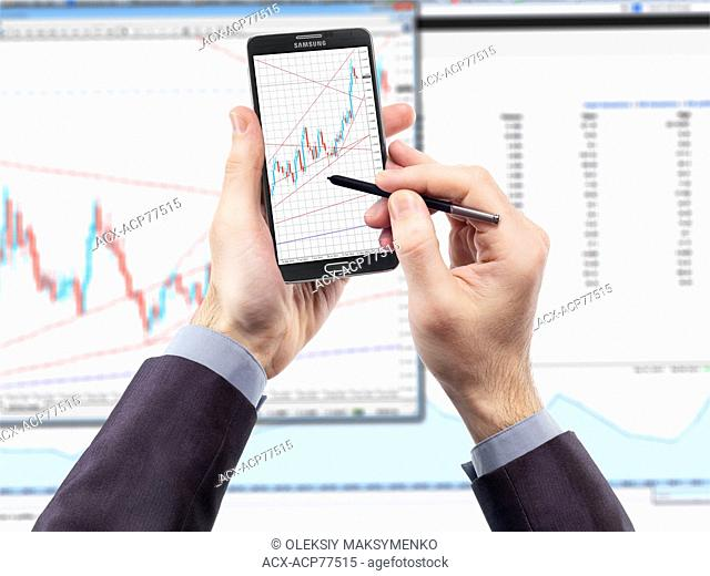 Businessman with smartphone displaying currency exchange charts and a monitor in the background