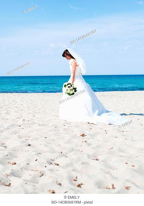 bride on beach holding bridal bouquet