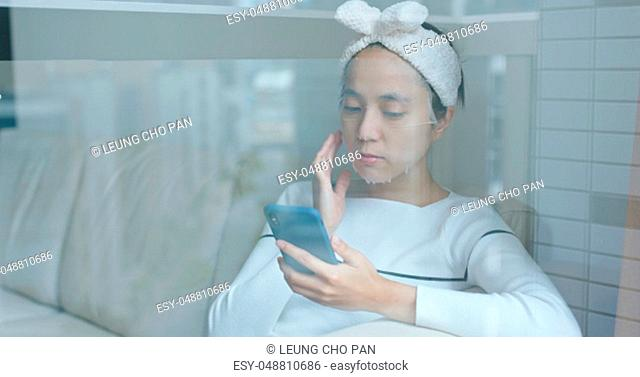 Woman apply paper mask and use of mobile phone at home with window reflection