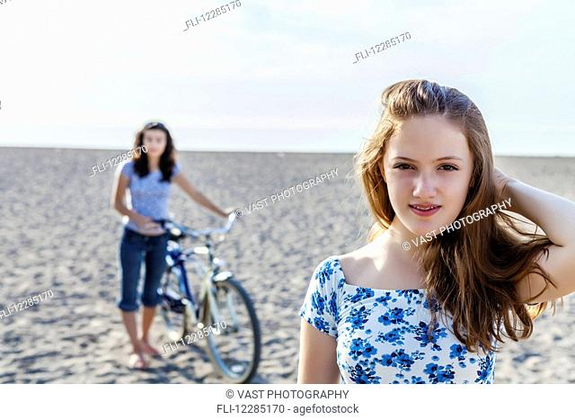 Two girls standing on a beach with bike; Toronto, Ontario, Canada