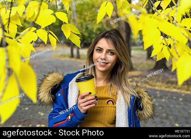 Girl in a yellow sweater with a paper cup of coffee on a background of autumn foliage