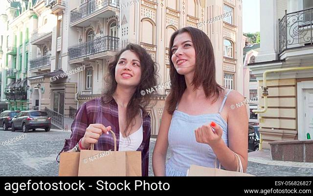 Two young women looking around in the city carrying shopping bags. Female friends enjoying sightseeing together after shopping at the mall