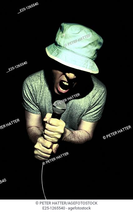 Adult wearing a hat and gray tee shirt male sings in to microphone. Isolated on black background