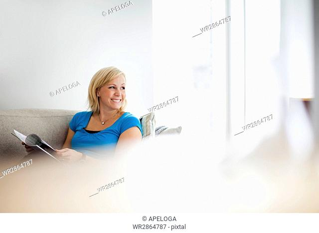 Happy woman holding book while looking away at home