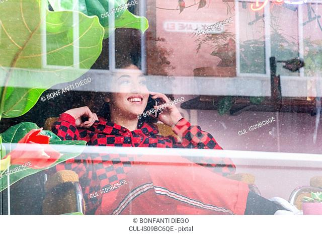 Young woman sitting indoors, using smartphone, viewed through window