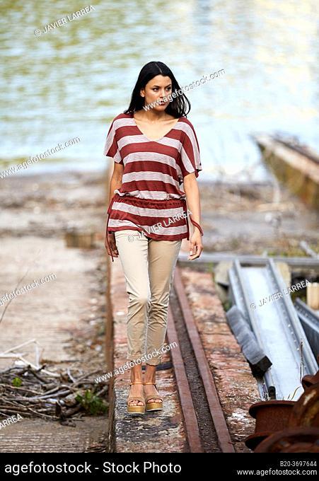 Young woman walking in shipyard, ship in the port of Pasaia, Gipuzkoa, Basque Country, Spain, Europe