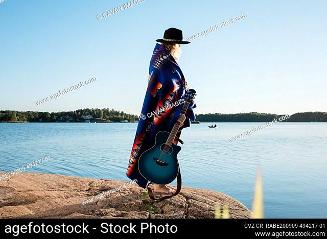 woman wrapped in a Pendleton blanket holding her guitar at the beach