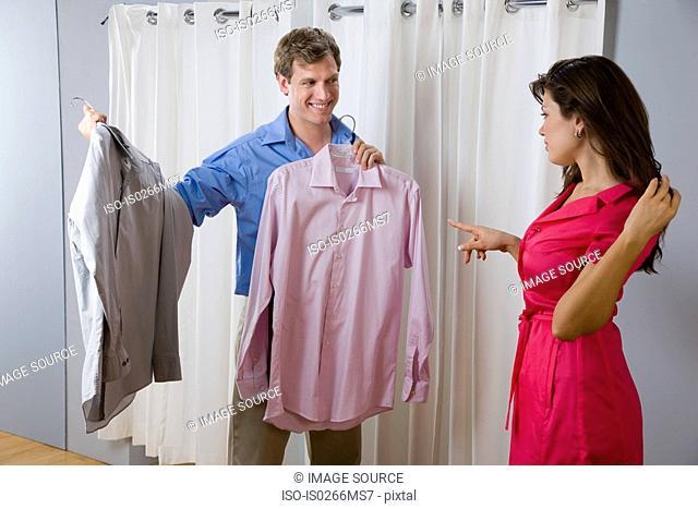 A woman helping a man choose a shirt