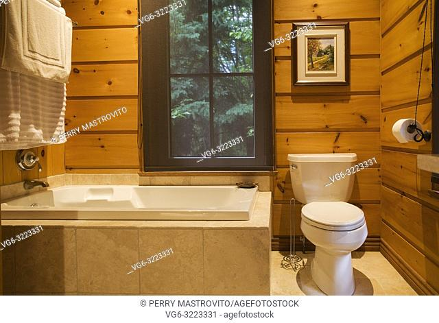 Bathroom with white porcelain toilet inside a milled piece sur piece cottage style flat log profile home