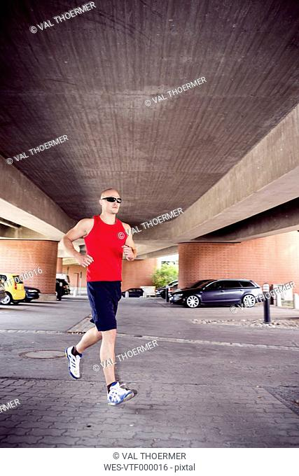 Man jogging under a bridge