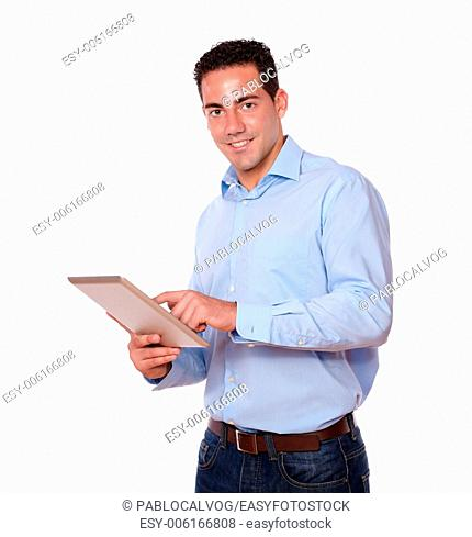 Portrait of a young hispanic man on blue shirt using his tablet pc while smiling at you on isolated studio