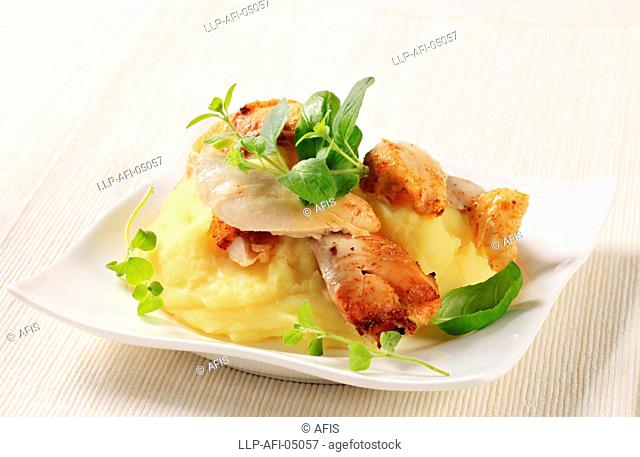 Pieces of roasted chicken on bed of mashed potato