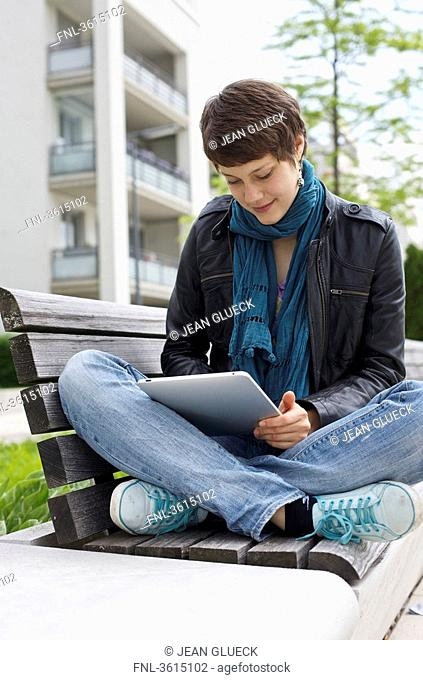 Young woman using iPad on a bench