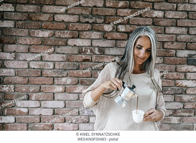 Woman with long grey hair pouring coffee into cup