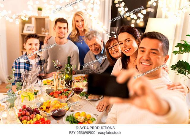 family having dinner party and taking selfie