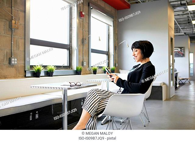 Businesswoman sitting at table in office environment, looking at smartphone