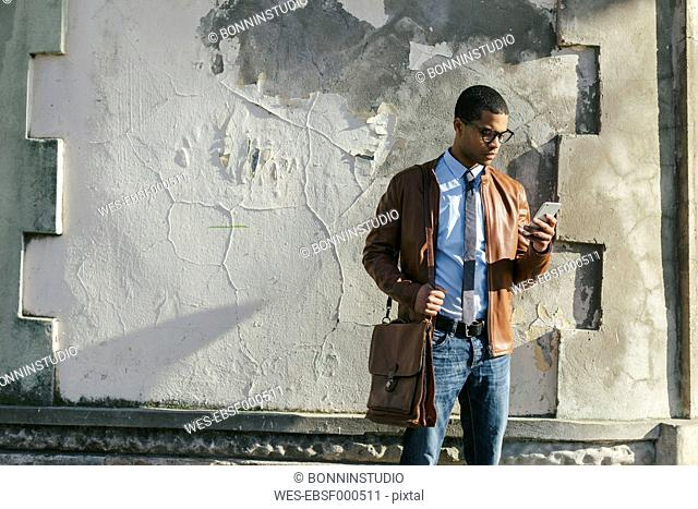 Businessman with smartphone wearing leather jacket and glasses
