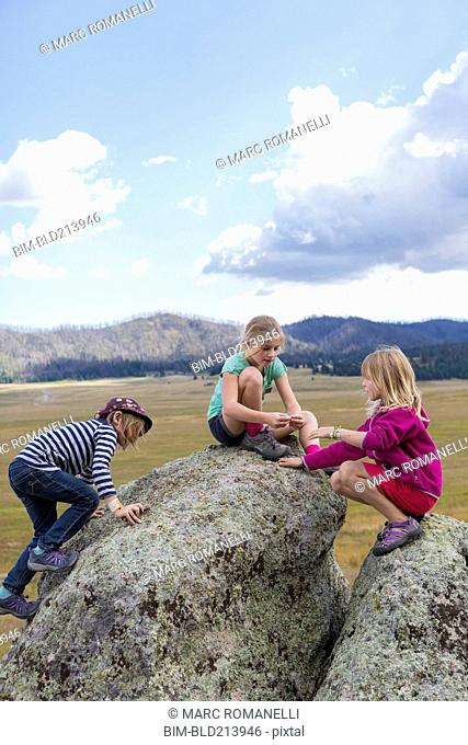 Children exploring rock formations in remote landscape