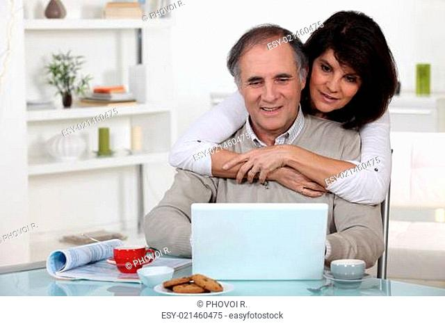 A middle age couple looking at a laptop