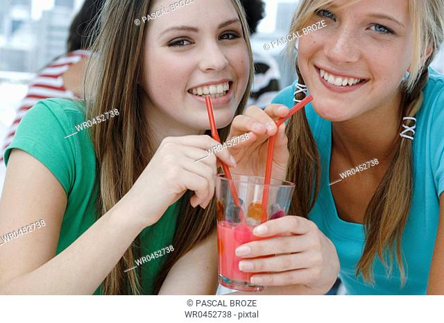 Portrait of two young women drinking juice in a restaurant