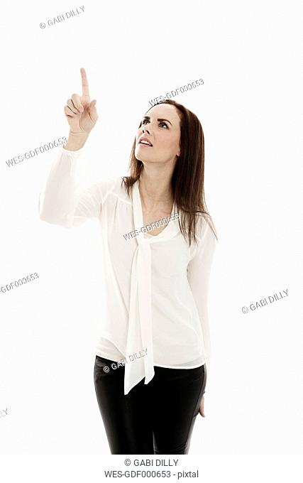 Portrait of young woman pointing on something in front of white background