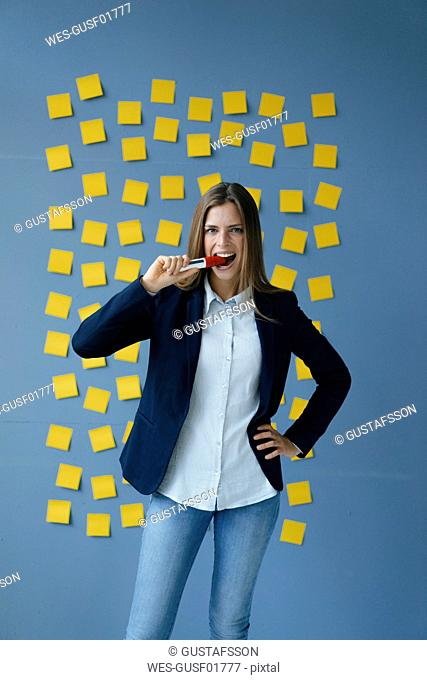 Yong businesswoman standing in front of wall, full of yellow sticky notes, biting marker pen