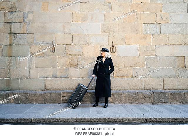Mature businesswoman wearing black coat and leather cap standing on pavement with rolling suitcase