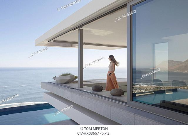 Woman looking at ocean view on modern, luxury home showcase exterior balcony