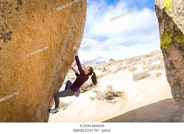 Mixed Race girl climbing rock